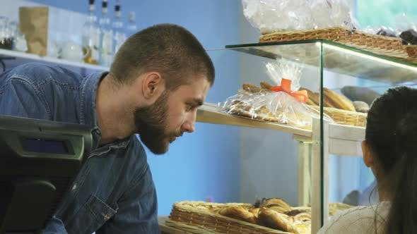 Cover Image for Attractive Male Baker Talking To a Little Girl at His Bakery Store