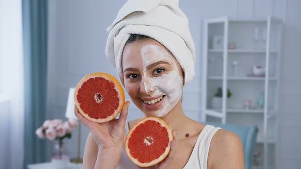Cover Image for Handsome Young Woman Posing with Two Half of Grapefruit with Mask on the Half of Face