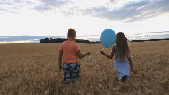 Thumbnail for Small Girl and Boy Holding Balloon in Hands and Walking Through Wheat Field at Sunset. Couple of