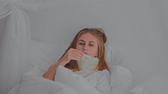 Young Woman Lies in Bed with a Scarf and a Thermometer is Sick