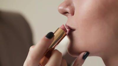 Woman Makeup Artist Applying Lip Gloss on Lips Makeup Model with Cosmetics Brush