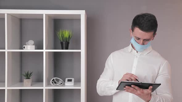 Thumbnail for Doctor in a Protective Medical Mask Works at a Tablet in His Office.