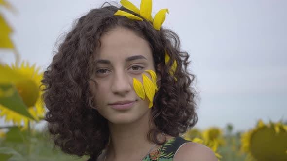 Thumbnail for Portrait of Beautiful Curly Playful Girl Looking at the Camera Standing on the Sunflower Field
