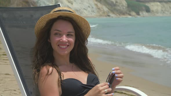 Beautiful Smiling Brunette Female Lying on the Deck Chair on the Beach