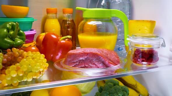 Fresh Raw Meat on a Shelf Open Refrigerator