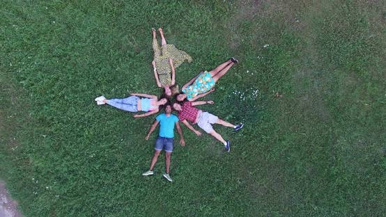 Thumbnail for Young happy friends forming a star shape lying in grass