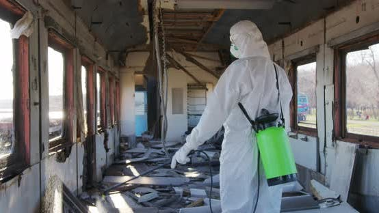 Virologist in Protective Costume and Respirator Disinfects Surfaces.