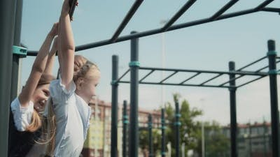 Schoolgirls Climbing On The Monkey Bars At A Schoolyard