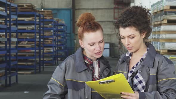 Thumbnail for Two Female Warehouse Workers Examining Documents Together