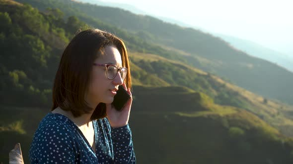 Thumbnail for A Young Woman in a Dress Sits and Speaks on the Phone Against a Background of Mountains. The Girl