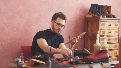Young Designer Using a Brush While Working in Shoe Shop with Modern Interior