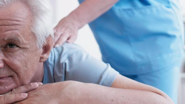 Masseur Massaging Back of Male Patient