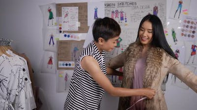 Teacher woman measuring tape on fashion student girl in studio.