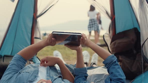 Couple Asia teenagers have relax time look photo album on tablet with happy moment togetherness.