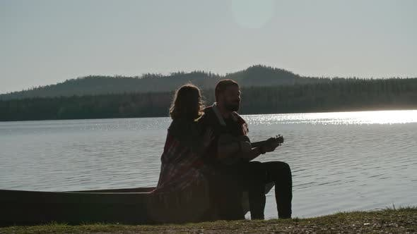 Cover Image for Boyfriend Playing Guitar to Girlfriend near Lake