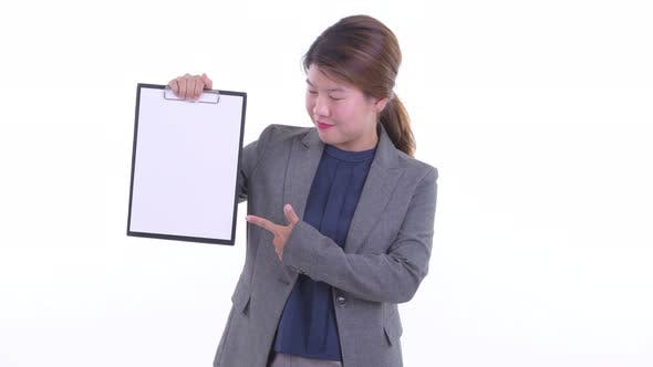 Thumbnail for Happy Young Asian Businesswoman Showing Clipboard and Giving Thumbs Up