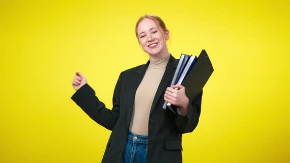 Cheerful Confident Female CEO with Toothy Smile Dancing with Documents at Yellow Background