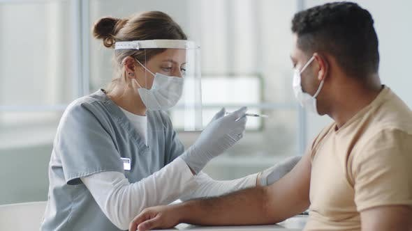 Nurse in Protective Uniform Vaccinating Patient