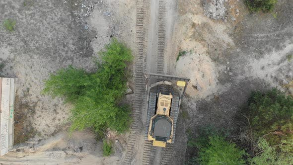 Thumbnail for Top Aerial View on Tracked Bulldozer Rides on Sandy Road at Construction Site