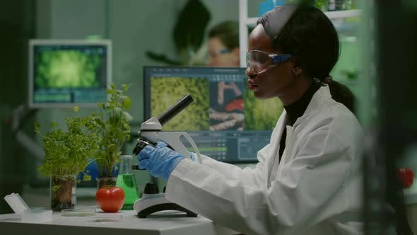 Biologist Woman Looking at Test Sample Under Microscope
