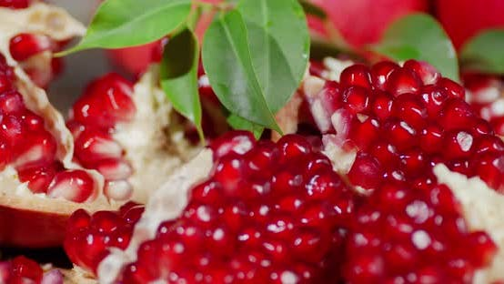 Pieces of Pomegranate with Leaves Slowly Rotate.