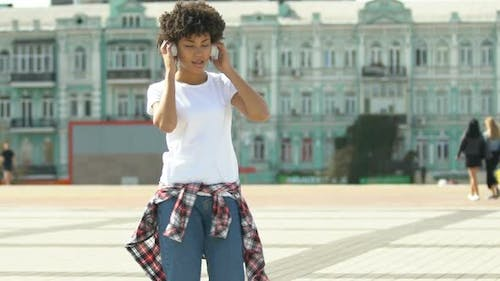 Woman Putting on Headphones and Dancing Outdoors, Freedom From Prejudice