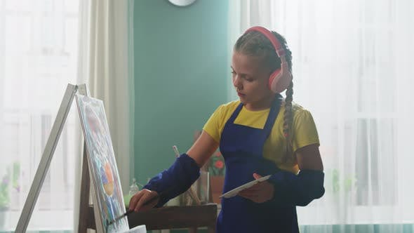 Small Girl In Wireless Headsets Is Painting