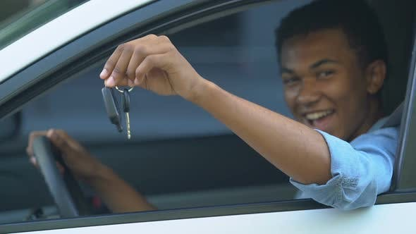 Happy black male teenager on driver place showing car keys