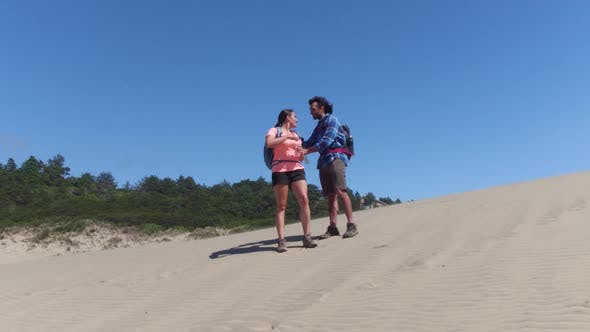 Thumbnail for Couple hiking on sand dunes and taking water break