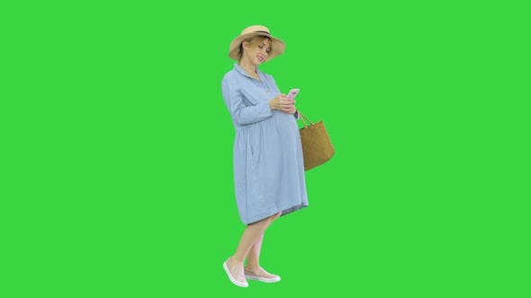 Pregnant Woman on the 9Th Month Using a Smartphone on a Green Screen Chroma Key