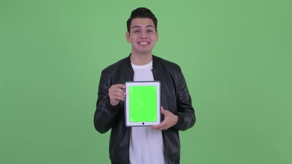 Thumbnail for Happy Young Handsome Multi Ethnic Man Showing Digital Tablet and Looking Surprised