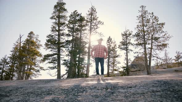 Amazing Low Angle Shot of Young Man Standing Alone on Big Rock with Sun Backlight Flare at Yosemite