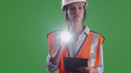 Thumbnail for Female engineer in hard hat shining flashlight into camera lens on greenscreen