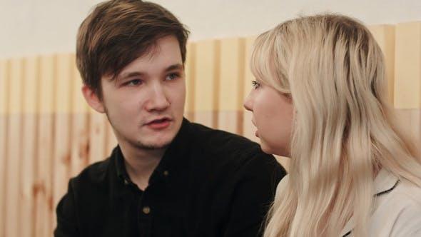 Thumbnail for Porträt des jungen Paares im Gespräch ernsthaft und trinken