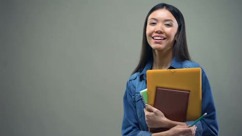 Asian Woman Standing With Copybooks on Grey Background