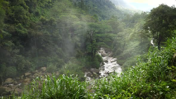 Thumbnail for Video of Fog Covering Small River in the Valley Between Two Mountains at Tropical Jungle Forest