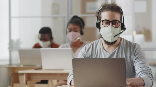 Thumbnail for Male Call Center Agent in Face Mask Working on Laptop in Office