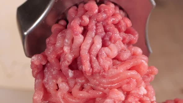 Filling Comes Out Through a Meat Grinder Sieve. Meat Grinder Close Up. Pile of Chopped Meat. Mincer