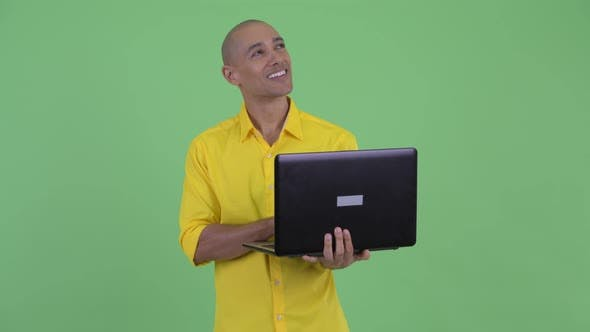 Cover Image for Happy Handsome Bald Businessman Thinking While Using Laptop