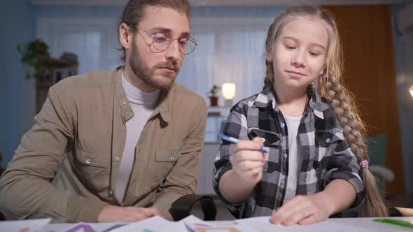 Portrait of Family During an Online Lesson Girl Writes in a Notebook and Then Gives Five to Her