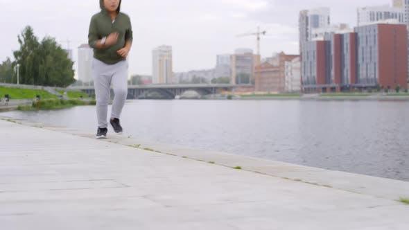 Thumbnail for Sportive Asian Boy Jogging along Urban Riverside in the Morning