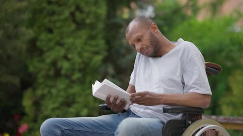 Engrossed Interested African American Disabled Reader in Wheelchair Enjoying Literature Outdoors on