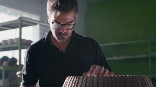 Adult Craftsman Creating Ornament on Clay Vessel
