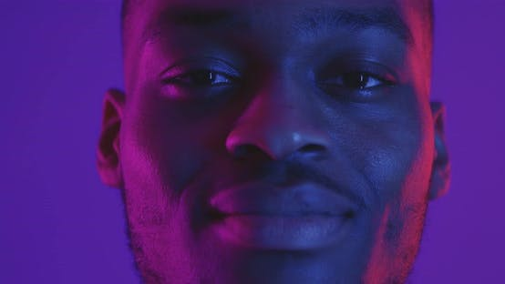 Close Up Portrait of African American Man Looking at Camera in Neon Light and Smiling
