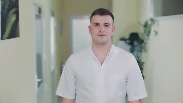 Porträt eines jungen Therapeuten, der in einem Krankenhauskorridor steht und in die Kamera blickt