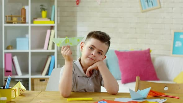 Cover Image for Cute Little Boy Smiling and Posing for Camera with Handmade Origami Boat
