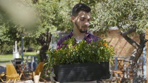 Porträt von Niedlich bärtigen Bauern halten ein Topf von Blumen in den Händen Blick auf Kamera lächelnd stehend