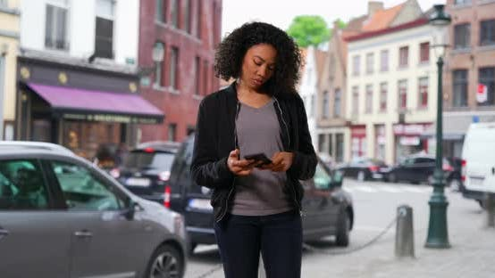 Thumbnail for Pretty black woman walking through the city, stopping to use her phone