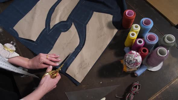 Thumbnail for Hands of Dressmaker Cutting Patterns with Scissors