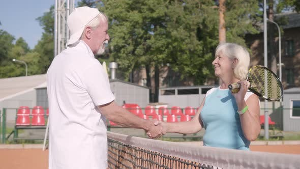 Adult Woman Shakes Hands with Handsome Mature Man Rival Standing on a Tennis Court in the Rays